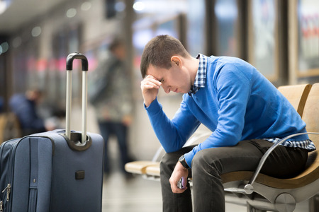 Photo pour Portrait of young handsome guy wearing casual style clothes waiting for transport. Tired traveler man travelling with suitcase sitting with frustrated facial expression on a chair in modern station - image libre de droit