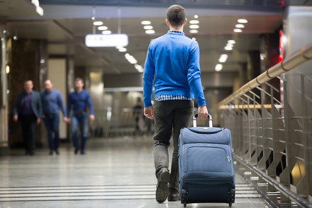 Foto de Young man pulling suitcase in modern airport terminal. Travelling guy wearing smart casual style clothes walking away with his luggage while waiting for transport. Rear view. Copy space - Imagen libre de derechos