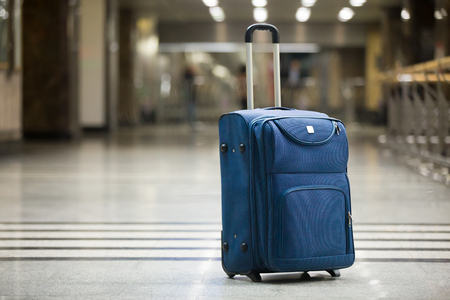 Foto de Large blue wheeled suitcase standing on the floor in modern airport terminal. Copy space - Imagen libre de derechos