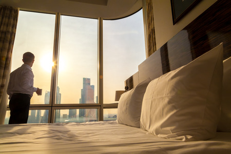 Photo pour Bed maid-up with white pillows and bed sheets in cozy room. Young businessman with cup of coffee standing at window looking at city scenery on the background. Focus on cushion - image libre de droit