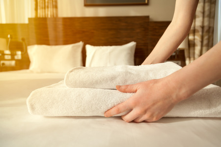 Foto de Close-up of hands putting stack of fresh white bath towels on the bed sheet. Room service maid cleaning hotel room. Lens flair in sunlight - Imagen libre de derechos