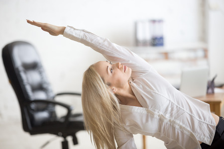Foto de Business and healthy lifestyle concept. Portrait of young office woman doing fitness exercise at workplace. Happy beautiful business lady doing side bending posture on her break time - Imagen libre de derechos