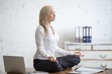 Photo pour Business and healthy lifestyle concept. Portrait of young office woman sitting cross-legged in half lotus yoga pose at workplace. Smiling business lady meditating after finishing her work - image libre de droit