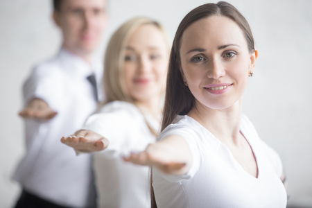 Foto de Business and healthy lifestyle concept. Portrait of young office workers standing in yoga pose at workplace. Smiling business people doing Warrior II posture, Virabhadrasana 2 pose on break time - Imagen libre de derechos