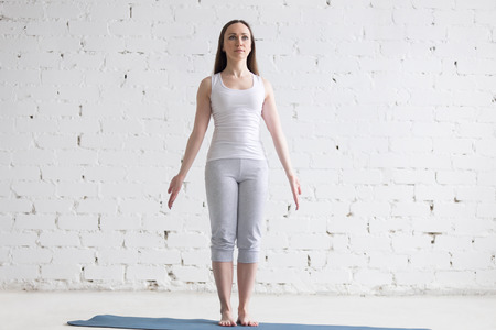 Foto de Attractive happy young woman working out indoors. Front view portrait of beautiful model doing yoga exercise on blue mat. Standing in Tadasana, Mountain Pose. Full length - Imagen libre de derechos