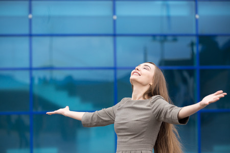 Foto de Portrait of cheerful young business woman standing with outstretched arms and relaxing outdoors with closed eyes. Happy beautiful caucasian woman feeling ecstatic on the street in summer. Copy space - Imagen libre de derechos