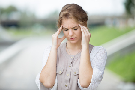 Foto de Portrait of stressed beautiful woman walking on the street and holding her head with hands trying to remember something or having headache. Attractive model suffering from pain outdoors in summer - Imagen libre de derechos