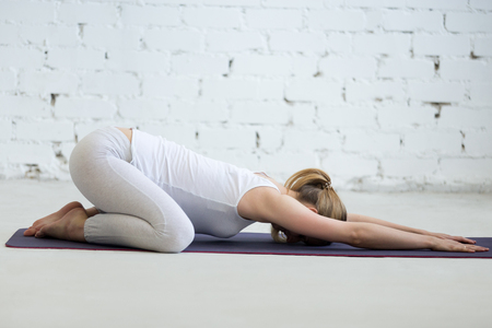Photo pour Pregnancy Yoga and Fitness. Portrait of young pregnant yoga model working out in loft with white walls. Pregnant fitness person practicing yoga at home. Prenatal Balasana, Child Pose - image libre de droit