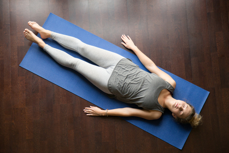 Photo pour Attractive young woman working out at home, doing yoga exercise on blue mat, lying in Shavasana Corpse or Dead Body Pose , resting after practice, meditating, breathing. Full length, view from above - image libre de droit