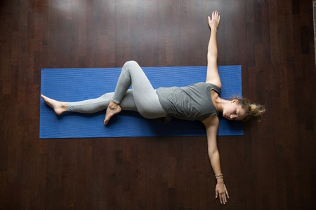 Photo pour Attractive young woman working out indoors, doing yoga exercise on wooden floor, lying in Reclining Spinal Twist, Jathara Parivartanasana, resting after practice, full length, top view - image libre de droit