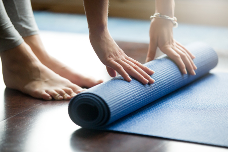 Photo pour Close-up of attractive young woman folding blue yoga or fitness mat after working out at home in living room. Healthy life, keep fit concepts. Horizontal shot - image libre de droit