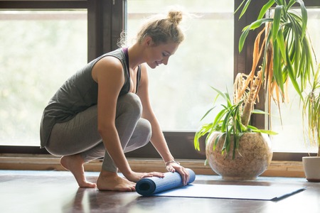 Photo pour Full length portrait of happy attractive young woman folding blue yoga or fitness mat after working out at home in living room. Healthy life, keep fit concepts. Horizontal image - image libre de droit