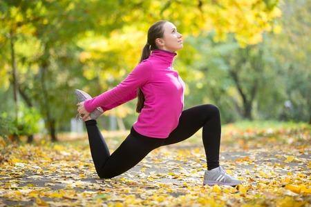 Foto de Sporty beautiful happy young woman practicing yoga, standing in Hip Flexor Low Lunge, Anjaneyasana pose, working out outdoor on autumn day wearing sportswear sweatshirt. Full length - Imagen libre de derechos