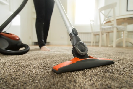 Foto de Close up of the vacuum cleaner, focus on the brush, woman cleaning the carpet. Home, housekeeping concept - Imagen libre de derechos
