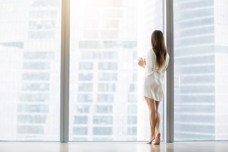 Photo pour Young woman, wearing dress gown looking through floor window, waiting for a busy husband, dreaming of a job in big city, first day in unknown town, ready to conquer the capital. Rear view, full length - image libre de droit