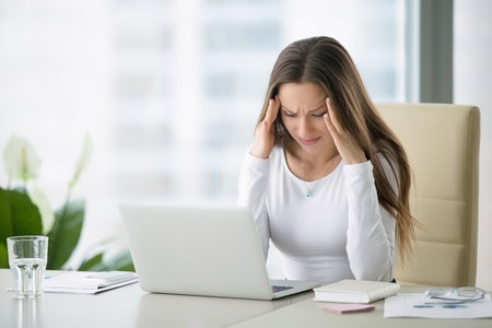 Foto de Young frustrated woman working at office desk in front of laptop suffering from chronic daily headaches, treatment online, appointing to a medical consultation, electromagnetic radiation, sick pay - Imagen libre de derechos
