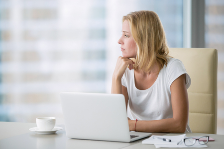 Photo for Young attractive woman at a modern office desk, working with laptop, looking at the window, thinking about a post, seeking for inspiration, help to be productive, updating computer - Royalty Free Image