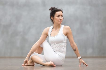 Foto de Beautiful young woman with floral tattoo working out against grey wall, doing yoga or pilates exercise. Girl sitting in Half lord of the fishes, Ardha Matsyendrasana pose. Full length - Imagen libre de derechos