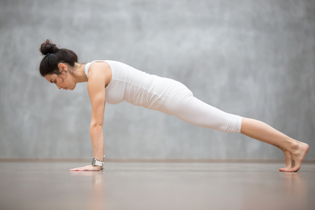 Photo pour Beautiful young woman wearing white sportswear set and smartwatch working out against grey wall, doing yoga or pilates exercise. Push ups or press ups, Plank, phalankasana pose. Full length - image libre de droit
