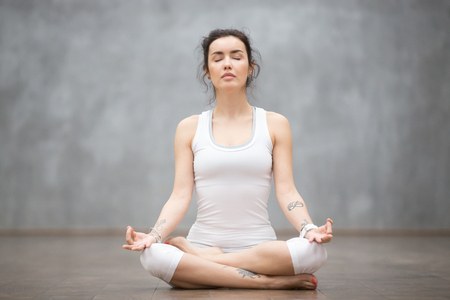 Photo pour Front view portrait of beautiful young woman with floral tattoos working out against grey wall, resting after doing yoga exercises, sitting in ardha Padmasana, Lotus pose, relaxing. Full length - image libre de droit