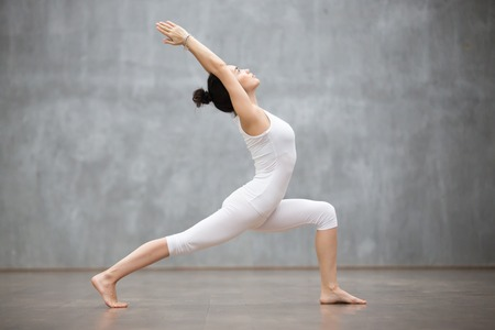 Photo pour Side view portrait of beautiful young woman wearing white tank top working out against grey wall, doing yoga or pilates exercise. Standing in Warrior one pose, Virabhadrasana. Full length - image libre de droit