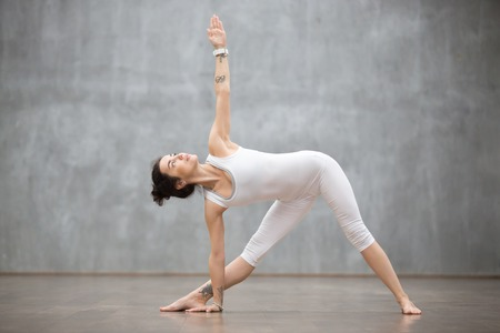 Photo for Profile portrait of beautiful young woman wearing white sportswear working out against grey wall, doing yoga or pilates exercise. Standing in Utthita Trikonasana, extended triangle pose. Full length - Royalty Free Image