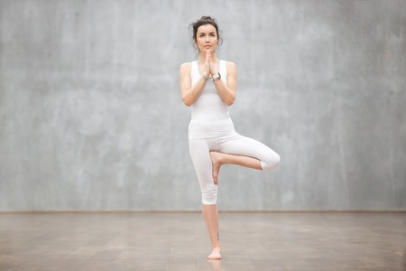 Foto de Portrait of beautiful young woman wearing white sportswear working out against grey wall, doing yoga or pilates exercise. Standing in Vrksasana, Tree pose. Full length - Imagen libre de derechos
