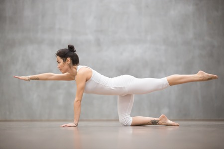 Foto de Side view portrait of attractive young woman with beautiful tattoo working out against grey wall, doing yoga, pilates balancing exercise. Bird dog, chakravakasana pose. Full length - Imagen libre de derechos