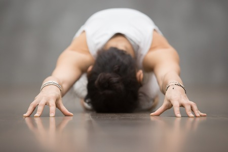 Photo pour Attractive young woman wearing white sportswear working out against grey wall, doing yoga, pilates exercise. Child Pose, Balasana pose. Focus on hands - image libre de droit