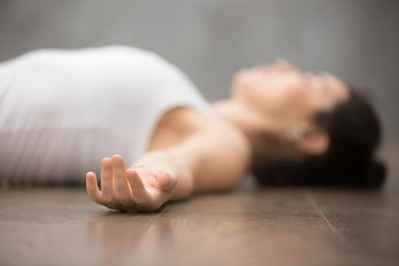 Photo pour Beautiful young woman working out on wooden floor, resting after doing yoga exercises, lying in Shavasana Corpse or Dead Body Posture , relaxing. Close up, focus on hand - image libre de droit
