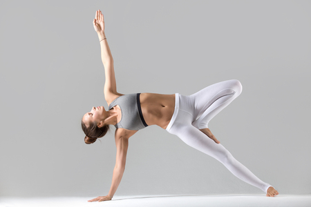 Photo for Young attractive woman practicing yoga, stretching in Side Plank exercise, Vasisthasana pose, working out wearing sportswear, white pants, indoor full length, isolated against grey studio background - Royalty Free Image