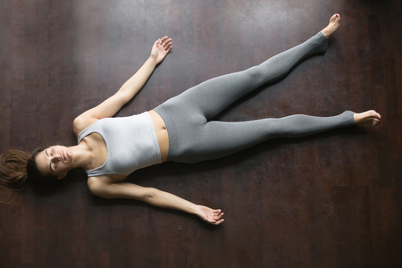 Foto de Beautiful young woman working out at home, doing yoga exercise on wooden floor, lying in Shavasana Corpse or Dead Body Posture , resting after practice, meditating, breathing. Full length, top view - Imagen libre de derechos