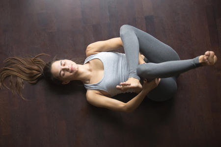 Photo pour Beautiful young model working out at home, doing yoga exercise on floor, lying in Eye of the Needle hip stretch pose Dead or Reclining Pigeon posture , resting after practice. Full length, top view - image libre de droit