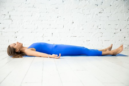 Photo pour Young attractive woman practicing yoga, lying in Dead Body, Corpse exercise, Savasana pose, working out wearing sportswear, blue suit, indoor full length, white loft studio background. Copy space - image libre de droit