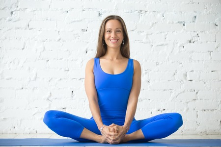 Foto de Young attractive woman practicing yoga, sitting in Butterfly exercise, baddha konasana pose, working out, wearing sportswear, blue suit, indoor full length, white loft studio background - Imagen libre de derechos