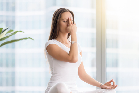 Photo pour Young attractive woman practicing yoga exercise, sitting in Sukhasana pose, performing Alternate Nostril Breathing technique, nadi shodhana pranayama, working out, wearing white sportswear, indoor - image libre de droit
