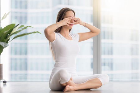 Photo pour Young woman practicing yoga, sitting in Sukhasana pose, performing Humming Bee Breathing exercise, Bhramari Pranayama technique, working out, wearing sportswear, white t-shirt, pants, full length - image libre de droit