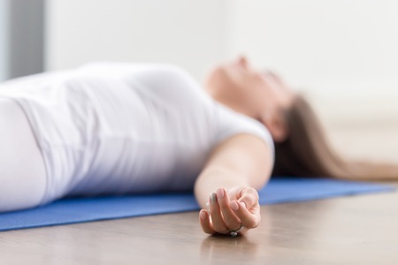 Foto de Closeup of young attractive woman practicing yoga, lying in Savasana exercise, Dead Body, Corpse pose, working out, wearing sportswear, white t-shirt, indoor, fingers in focus - Imagen libre de derechos