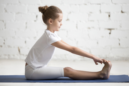 Foto de Girl child practicing yoga, stretching in paschimottanasana exercise, seated forward bend pose, working out, wearing sportswear, indoor full length, white loft studio background - Imagen libre de derechos