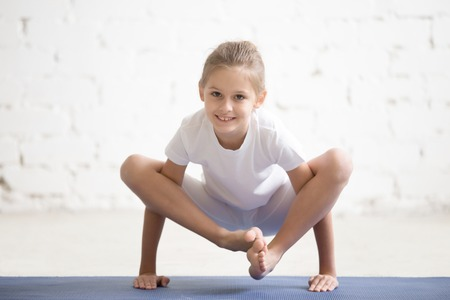 Photo for Portrait of smiling yogi girl child practicing yoga, standing in Bhuja Pidasana exercise, bhujapidasana pose working out wearing sportswear, indoor full length, white loft studio background - Royalty Free Image