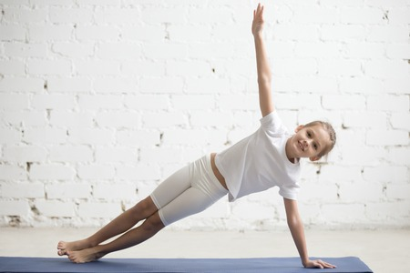 Photo pour Portrait of smiling girl child practicing yoga, standing in Vasisthasana exercise, Side Plank pose, working out wearing sportswear, t-shirt, pants, indoor full length, white studio background - image libre de droit
