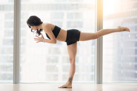 Photo pour Young attractive woman practicing yoga, standing in Warrior III, Virabhadrasana three pose, working out, wearing sportswear, black tank top, shorts, full length, near floor window, city view - image libre de droit