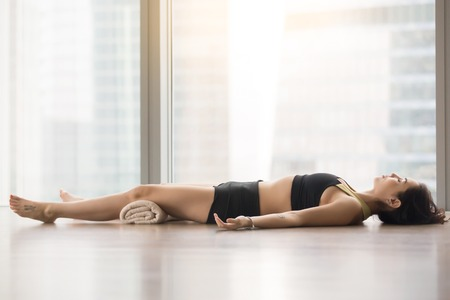 Photo pour Young sporty woman practicing yoga, lying in Corpse, Dead Body exercise, Savasana pose, working out, wearing sportswear, black tank top, shorts, indoor full length, near floor window with city view - image libre de droit
