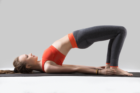 Foto de Young happy attractive woman practicing yoga, doing dvi pada pithasana exercise, Glute Bridge pose, working out, wearing sportswear, red tsports bra, pants, indoor full length, isolated, grey studio - Imagen libre de derechos