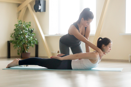 Photo pour Young beautiful lady beginning yoga practice with private teacher at home class, working out with professional female yogi instructor. Trainer helps student to do Salabhasana exercise, Locust pose - image libre de droit