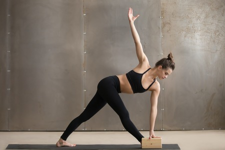 Photo pour Young attractive yogi woman in black practicing yoga, standing in Utthita Trikonasana exercise using block, extended triangle pose, working out, cool urban style, full length, grey studio background - image libre de droit