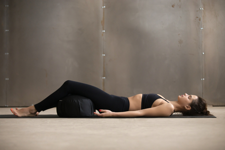 Foto de Young attractive sporty yogi woman practicing yoga, lying in Savasana exercise, Dead Body, Corpse pose using Zafu cushion for comfort, resting after working out, urban style grey studio, full length - Imagen libre de derechos