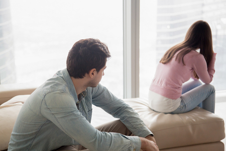 Foto de Young couple sitting apart indoors after quarrel. Offended girl ignoring boyfriend, looking away, serious man thinking about problem in relationships, family conflict, misunderstanding between teens - Imagen libre de derechos