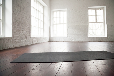 Photo for Empty white space in fitness center, white brick walls, natural wooden floor and big windows, modern loft studio, unrolled yoga mat on the floor, comfortable open area for sport and exercises - Royalty Free Image