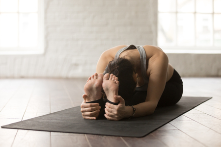 Photo for Young attractive yogi woman practicing yoga concept, sitting in paschimottanasana exercise, Seated forward bend pose, working out on black mat, wearing sportswear, white loft studio background - Royalty Free Image